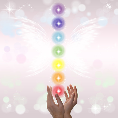 energy channels: Healing Hands and seven chakras on a sparklingpastel coloured background Stock Photo