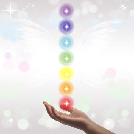 universal healer: Healing Hands and seven chakras on a sparklingpastel coloured background Stock Photo