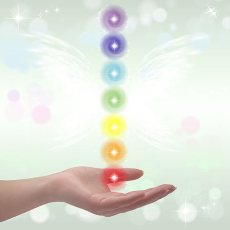 universal enlightenment: Healing Hands and seven chakras on a sparklingpastel coloured background Stock Photo