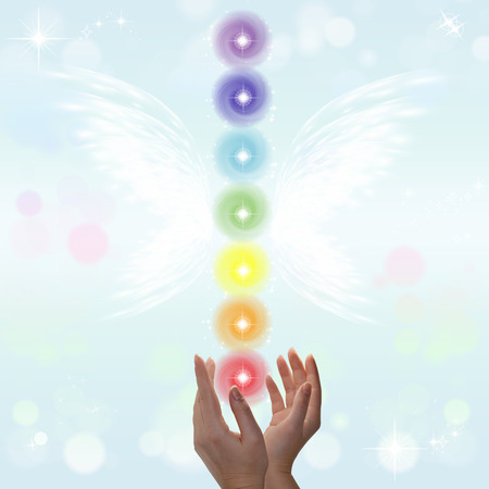 color healing: Healing Hands and seven chakras on a sparklingpastel coloured background Stock Photo