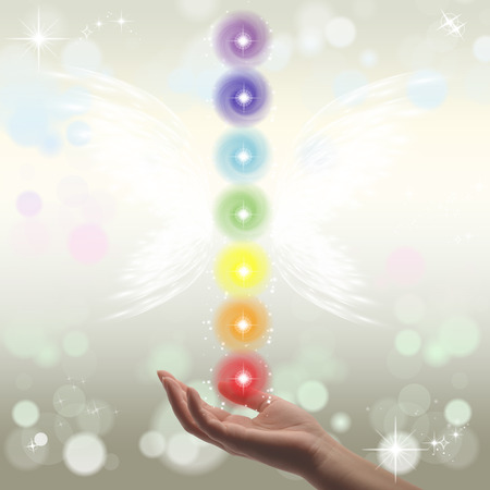 Healing Hands and seven chakras on a sparklingpastel coloured background Stock Photo