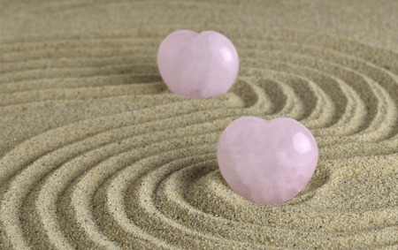 Rose quartz hearts placed in zen garden