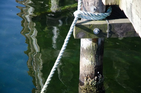 rope tied to dock good reflections in ocean Stockfoto