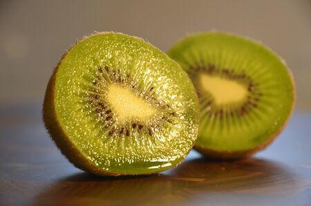 Kiwi fruit sliced on wooden board, close up