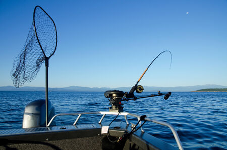 Fishing rod on bow of boat with landing net  Stockfoto