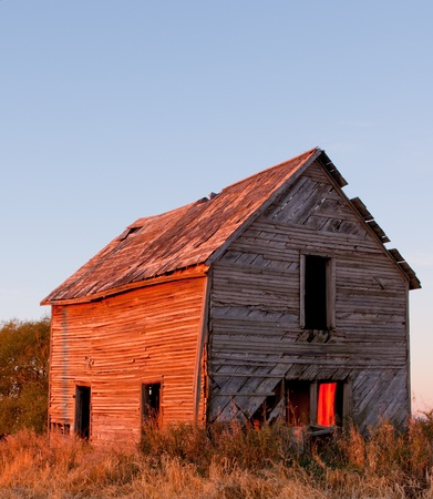 Old farm house on the prairie in southern Alberta at sunrise photo