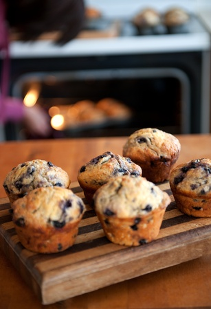 a woman baking blueberry muffins in her kitchen for a charity bake sale 스톡 콘텐츠