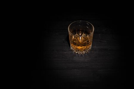 a glass of whiskey on a black wooden background. dark photo Stock Photo