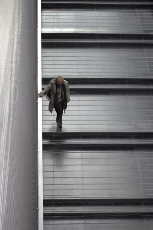 bajando escaleras: anciana con chaqueta clara y pantal�n oscuro bajando escaleras con una amplia baldosas negras y pasamanos de metal Foto de archivo