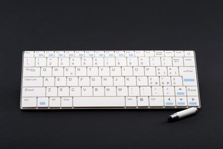 trato amable: Teclado inal�mbrico y blanca capacitiva l�piz stylus pen llamado tambi�n para las tabletas y tel�fonos inteligentes sobre un fondo negro