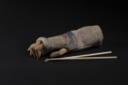 Wooden hand with winter glove and chopsticks for Chinese food on a black background