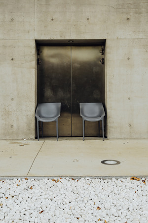 Square concrete with gravel and two chairs lift Stock Photo