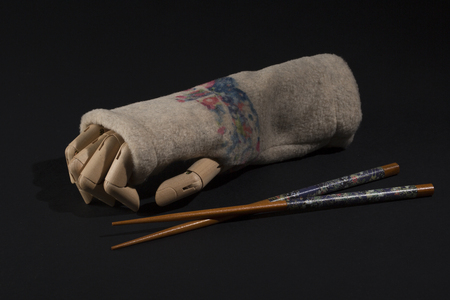 articulation: wooden hand with glove and wand Chinese food on a black background