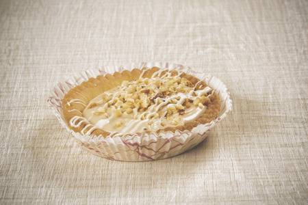 sweet pastry: Patty sweet tart hazelnut cream and crispy white chocolate and pastry on wood background