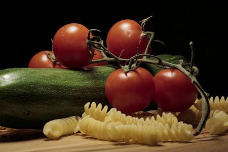 Zucchini spaghetti pasta tomatoes cherry chilli seeds on wooden cutting board Stock Photo