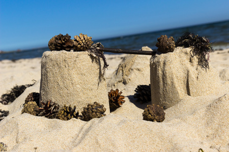 sand castle: Sand castle with pinecones on a beach. Stock Photo