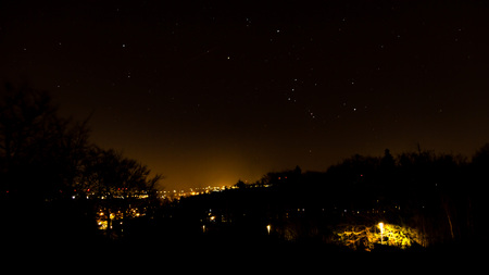 orion: The Orion constellation over city lights at night.