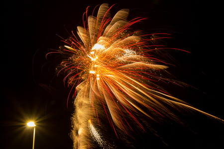 Red and yellow fireworks and a streetlight Stock Photo