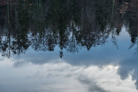 Clouds and trees reflections on the surface of the lake Reklamní fotografie