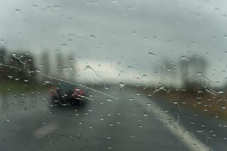 Windshiels full of raindrops and a highway