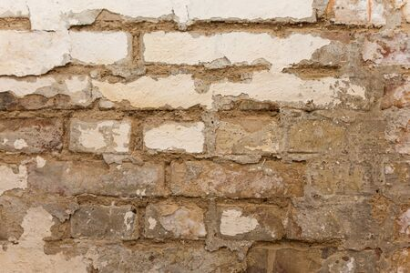 Rough brick wall with white paint coming loose