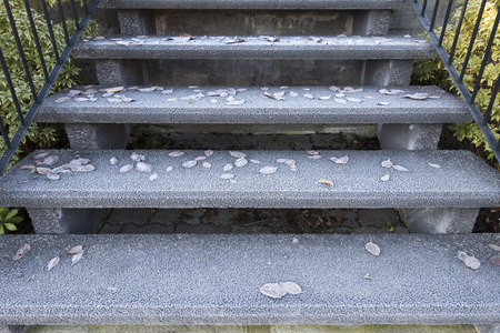 Frost and frozen leaves on slippery staircase
