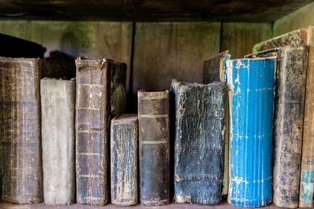 Old vintage books standing on a bookshelf