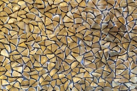 a wall of chopped firewood of a triangular shape. Texture. Banque d'images
