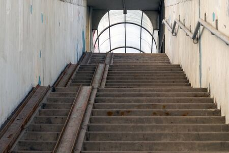Concrete overpass staircase with metal guides for running baby and wheelchairs in disrepair