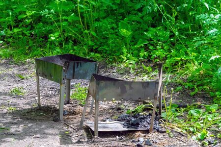 Two old broken metal braziers in a forest clearing with coal remains surrounded by greenery