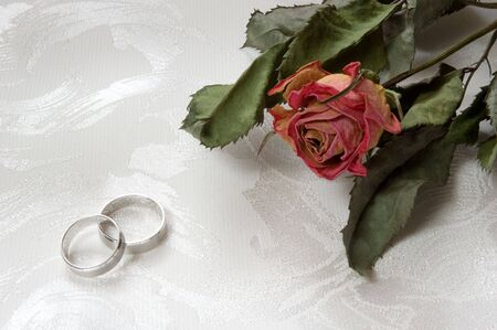 Two wedding rings and dry red rose on decorated cloth photo