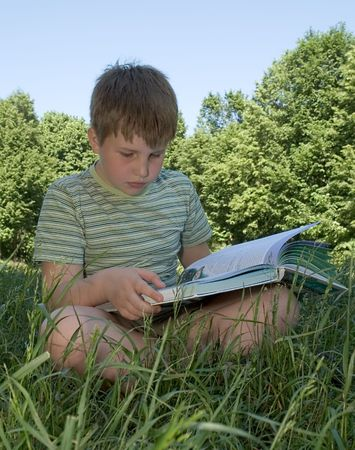 A little boy reads a big book with grass at background Stock Photo - 968299