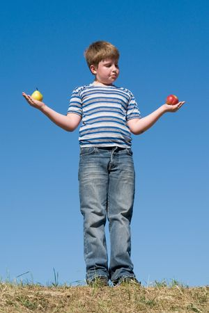 Difficult selection. Apple or pear? Boy with sky at background. photo