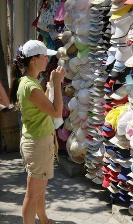 selects: Giovane donna seleziona cappuccio sul mercato.