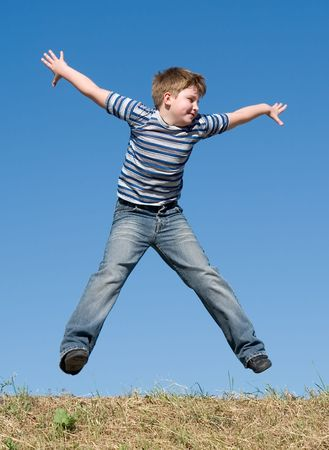 A little boy jumps with sky at background Stock Photo