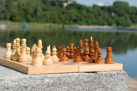 the chessboard with the figures with river at background photo