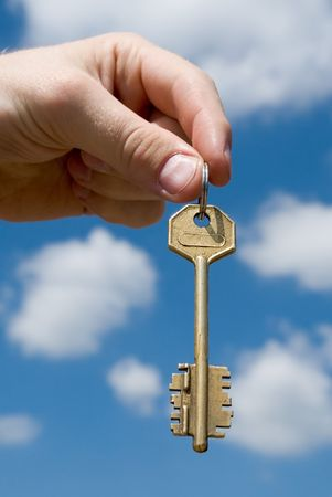 keys to heaven: hand transfers the key with sky at background Stock Photo