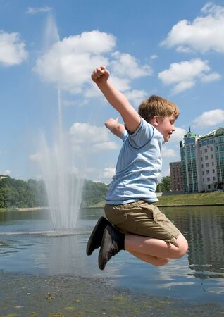 A little boy jumps with river at background  photo
