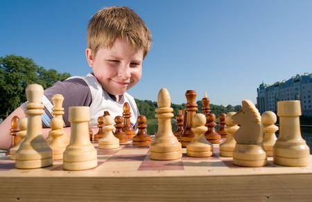 jugando ajedrez: Un peque�o ajedrez del muchacho con el cielo en el fondo Foto de archivo