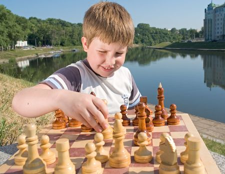 A little boy chess with river at background photo
