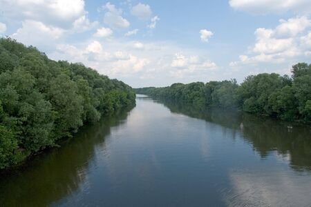 descriptive: Summer. River. Blue sky and green trees are reflected in water.