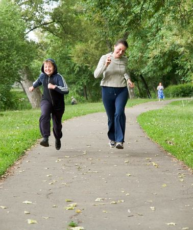 woman and boy run along the road photo