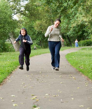 woman and boy run along the road photo