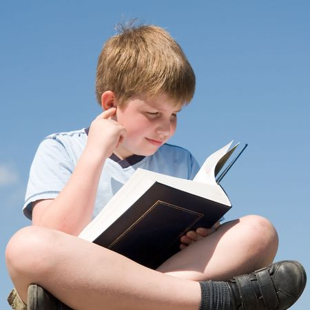 A little boy reads a big book with sky at background