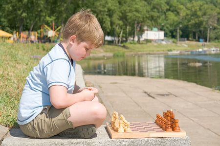 little boy chess with river at background photo