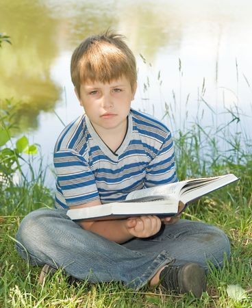 A little boy reads a big book with river at background photo