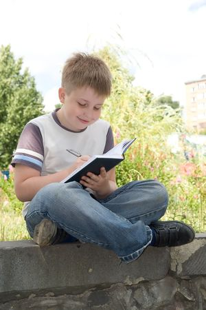 The little boy writes to writing-books