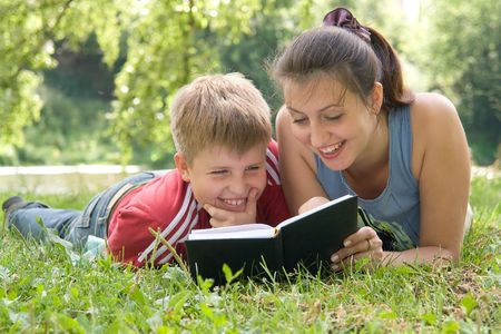Mum and the son reads the book on a lawn in park photo