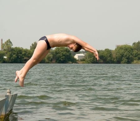 boy swim: The little boy jumps from a pier in water
