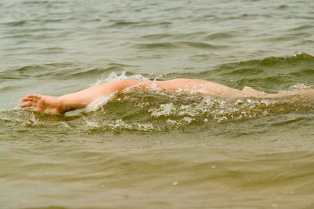 skin diving: the little boy quickly swims the crawl